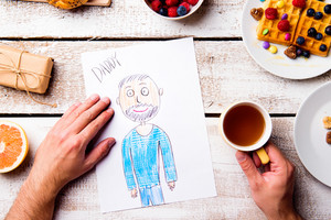 Fathers day composition. Hands of unrecognizable man with his childs drawing of him. Breakfast meal. Studio shot on wooden background.