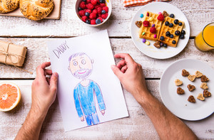 Fathers day composition. Hands of unrecognizable man with his childs drawing of him. Breakfast waffles with fruit. Studio shot on wooden background.