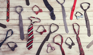 Fathers day composition of colorful ties and bow ties laid on wooden floor background.
