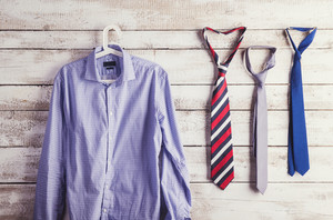 Fathers day composition of shirt and three ties hang on wooden wall background.