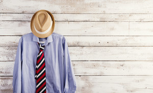 Fathers day composition of shirt, tie and hat hang on wooden wall background.