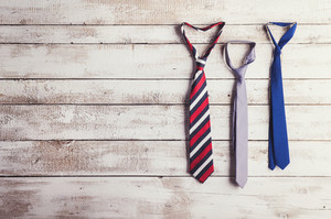 Fathers day composition of three ties hang on wooden wall background.