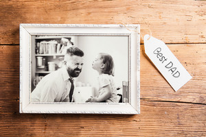 Fathers day composition. Photo of father and daughter in white picture frame. Studio shot on wooden background.