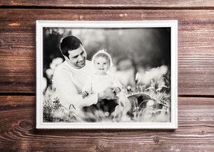Fathers day composition. Photo of father and son in white picture frame. Studio shot on wooden background.