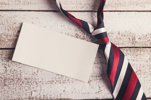 Fathers day composition - tie and empty sheet of paper. Studio shot on wooden background.