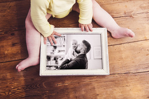Fathers day composition. Unrecognizable baby holding a photo of father and daughter in white picture frame. Studio shot on wooden background.