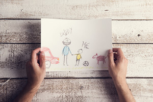 Fathers day composition with childs drawing held by a man laid on wooden desk backround.