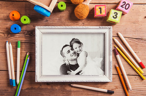 Fathers day concept. Black and white picture of father and his daugter in picture frame and toys on the floor. Studio shot on wooden background.