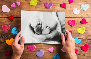 Fathers day concept. Hands of unrecognizable man holding black and white photo of father with his baby. Colorful fabric hearts. Studio shot on wooden background.
