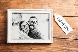Fathers day concept. Photo of father and daughter in white picture frame. Studio shot on wooden background.