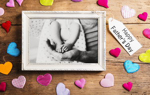 Fathers day concept. Picture frame with black and white photo of father with his baby. Colorful fabric hearts. Studio shot on wooden background.