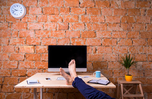 Feet of unrecognizable businessman sitting at his office desk. Brick wall background. Smart phone, tablet and various office supplies around the workplace. Flat lay.