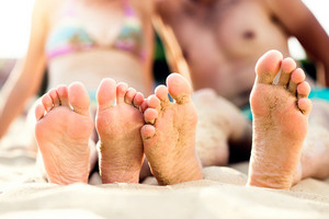 Feet of unrecognizable couple sitting on the sandy beach, sunny summer heat, barefoot