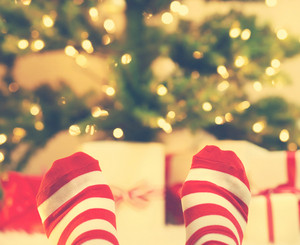 Feet with striped socks with Christmas gift boxes under the tree