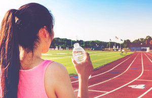 Female athlete drinking water on at a stadium running track
