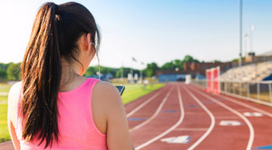 Female athlete listening to music on her smartphone on a stadium running track