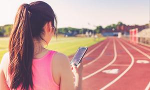 Female athlete listening to music on her smartphone on a stadium running track