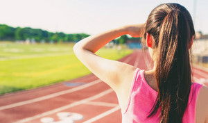 Female athlete looking out on a stadium track