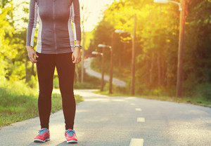 Female athlete preparing for a jog on a forest path at sunset