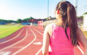 Female athlete running on at a stadium track