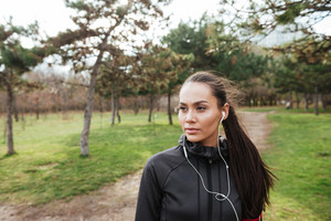 Female attractive runner in warm clothes and earphones in autumn park. Look aside.