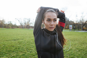 Female concentrated runner in warm clothes and headphones looking aside in autumn park while make sport exercise
