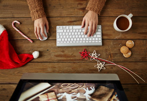 Female designer working with computer with coffee, biscuits and Christmas symbols on wooden table