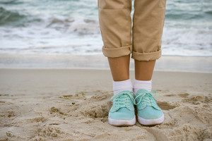 Female feet in beige pants and a turquoise sneakers standing on the beach. Walk along the beach in the autumn.