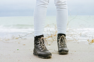 Female feet in blue jeans and black winter boots standing on the beach