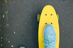 Female feet in blue sneakers on a yellow skateboard with green wheels riding on the road, top view