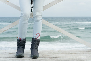 Female feet in jeans and sports boots on wooden boards against the sea close-up.