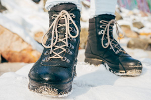 Female feet in winter boots with laces standing in the snow