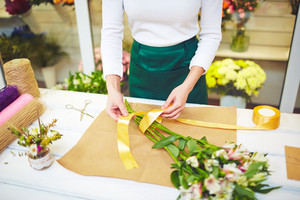 Female florist tying up bouquet of fresh flowers with yellow silk ribbon