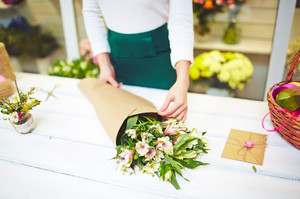Female florist wrapping up bouquet of white amaryllises