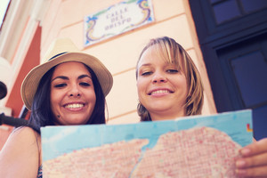 Female friends on holiday, young latina women having fun traveling. Two happy girls smiling in Havana, Cuba, using city map for directions.
