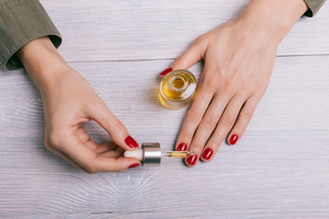 Female hand applied oil on the nails, the top view