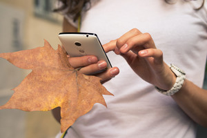 Female hand holding a mobile phone and fallen leaf close-up. A woman uses a mobile phone while walking.