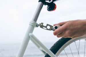 Female hand holds the tool to fix bike, close-up