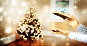 Female hand opening a gift box by a Christmas tree in a room
