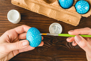 Female hand painted Easter eggs with a brush, top view