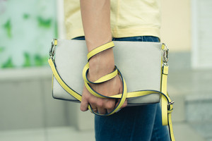 Female handbag gray-yellow in female hands close up. Young girl in blue jeans and a yellow T-shirt for a walk in the city.