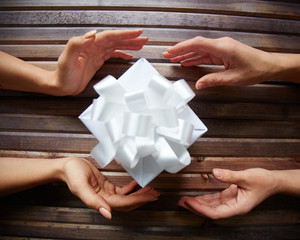 Female hands giving and taking gift-box on wooden background