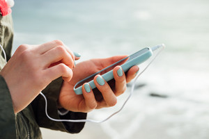 Female hands holding a blue mobile phone with the connected headphones on background of the sea