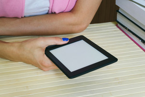 Female hands holding an e-book next to a stack of paper books