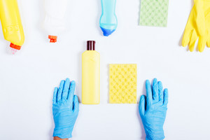 Female hands in blue rubber gloves, yellow and green bottle of detergent and sponge on white background, top view