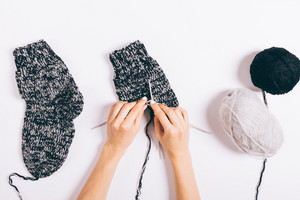 Female hands knit black wool socks on a white background, top view