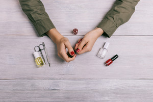 Female hands make manicure and paint nails with red lacquer. On the table are bottles of nail polish, scissors and other tools, top view.