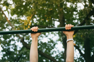 Female hands on the horizontal bar outdoors in the park. Sports activities on fresh air in the summer.