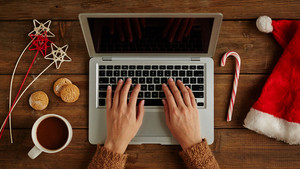Female hands typing on laptop with Christmas stuffs around