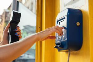 Female hands using the pay phone in the city